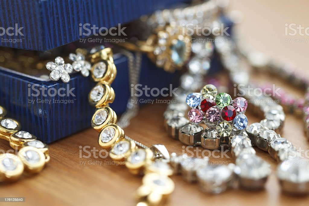 Small gift box with costume jewelry spilling out stock photo