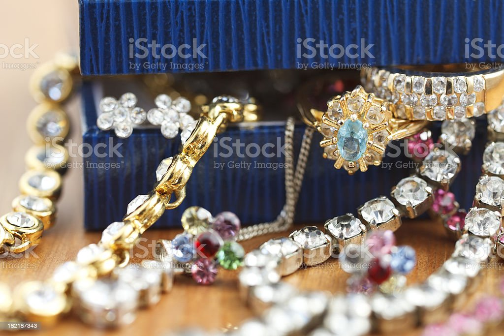 Small gift box with costume jewelry spilling out royalty-free stock photo