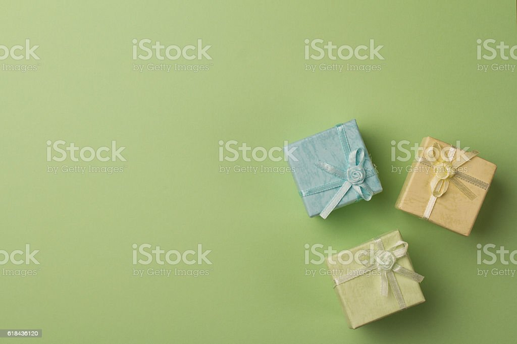 small gift boxes on green paper background stock photo