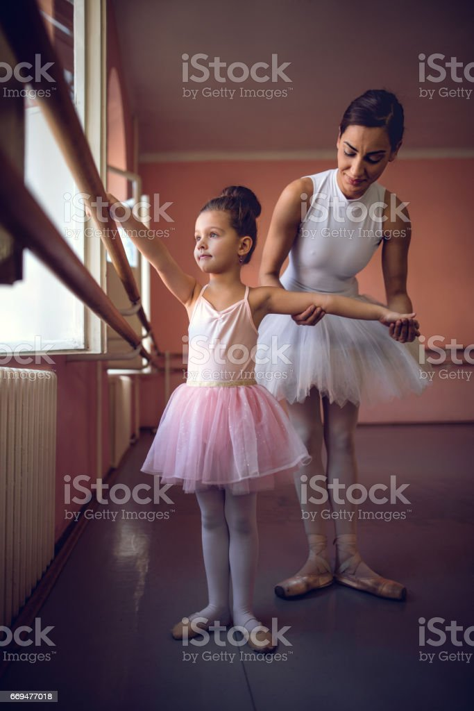 Small girl and ballet instructor during ballet class. stock photo