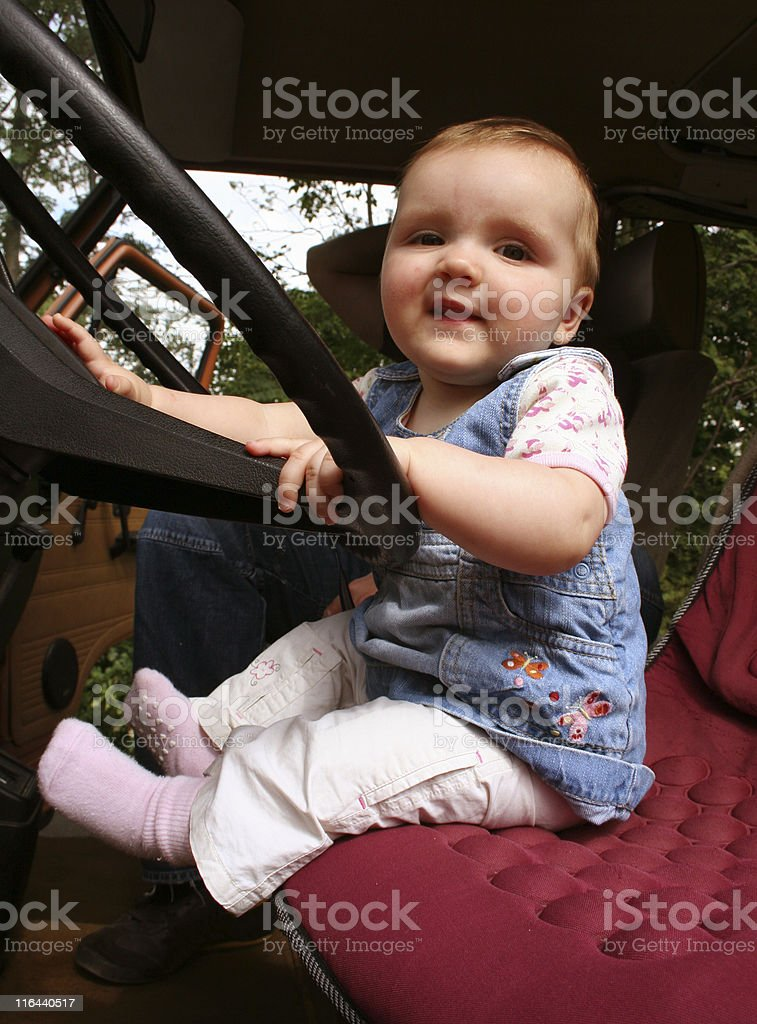 Small girl and big steering wheel royalty-free stock photo