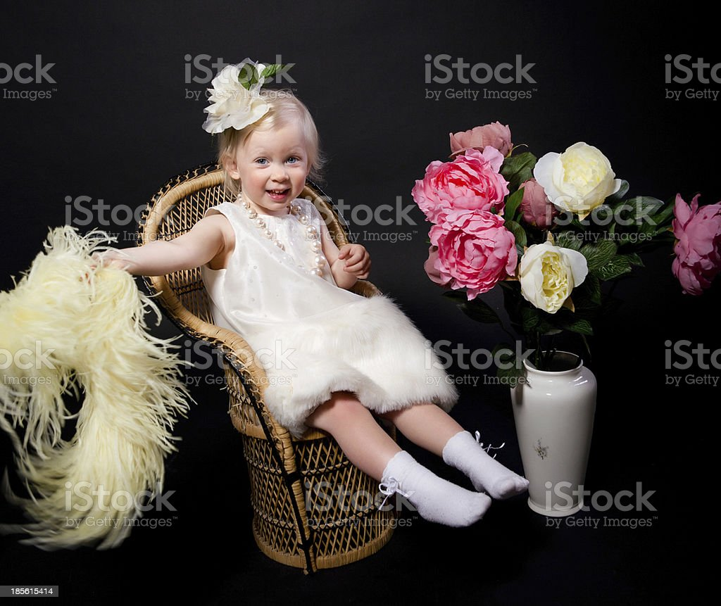 Small girl beautifully dressed holding feathers laughing/smiling royalty-free stock photo