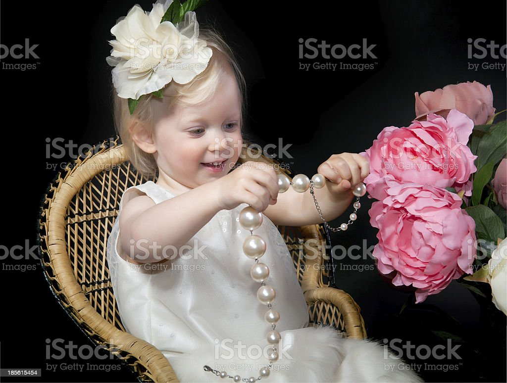 Small girl beautifully dressed holding pearl necklace smiling royalty-free stock photo