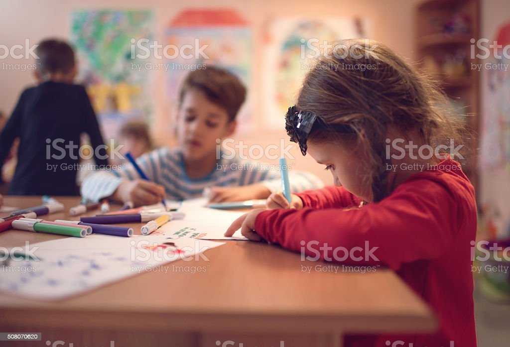 Small girl drawing on a class in a preschool. stock photo