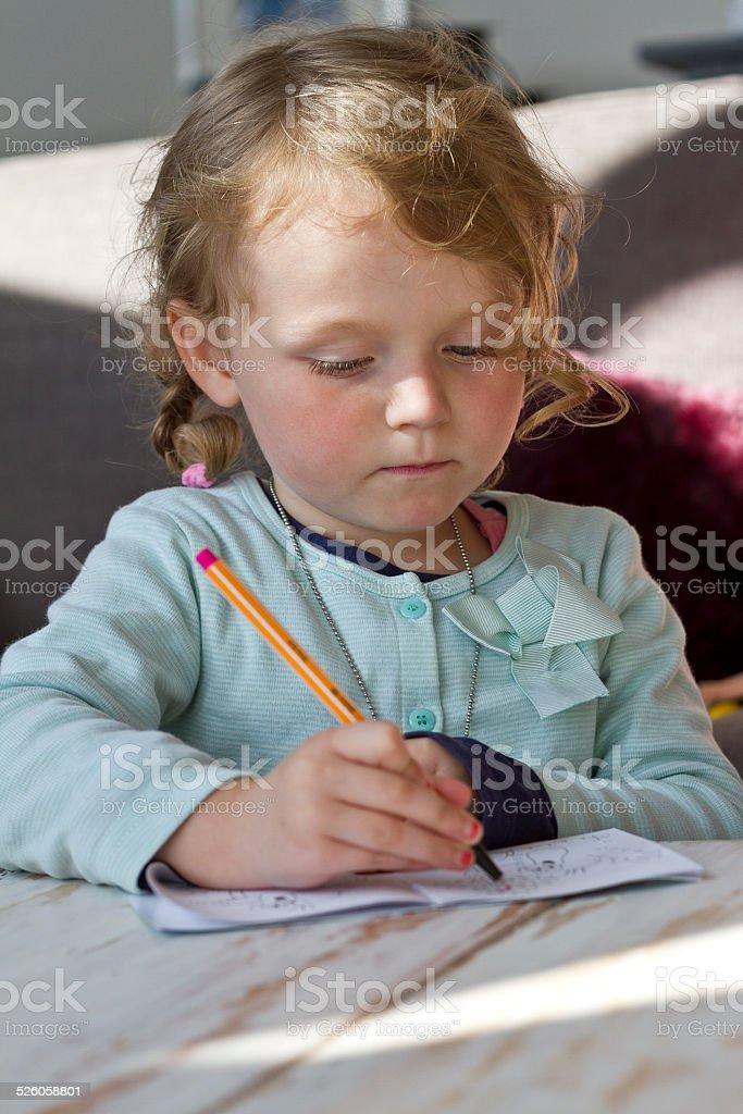 Small girl drawing stock photo