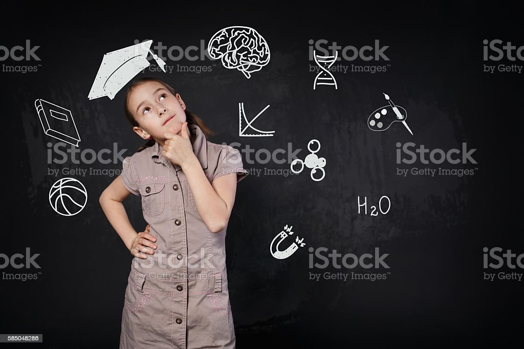 Small girl in imaginary graduation cap thinking about school stock photo