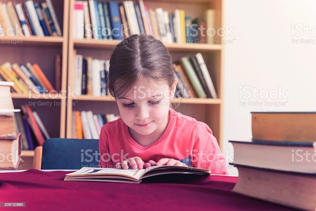 Small Girl in Old Library Reading Books stock photo