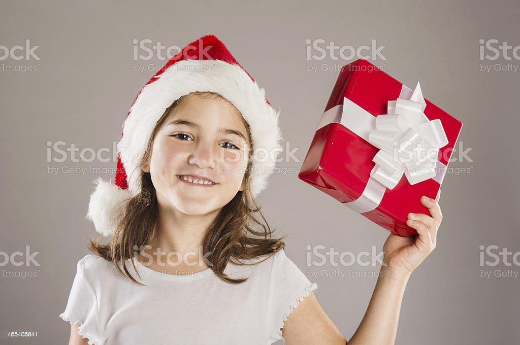 Small girl in santa hat with christmas gift stock photo