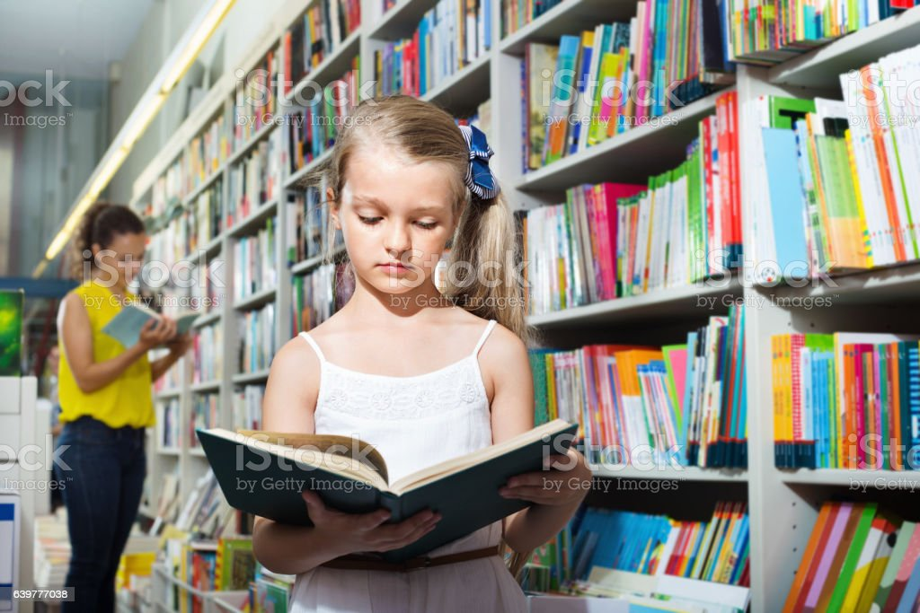 Small girl in school age standing with open book stock photo