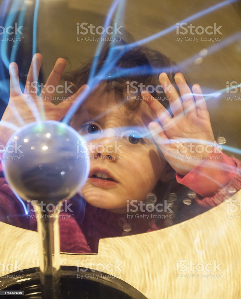 small girl looking into a plasma ball stock photo