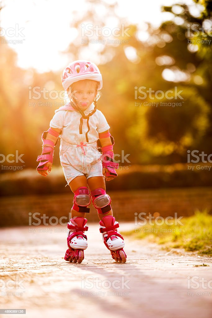 Small girl on rollerblades in the park. stock photo