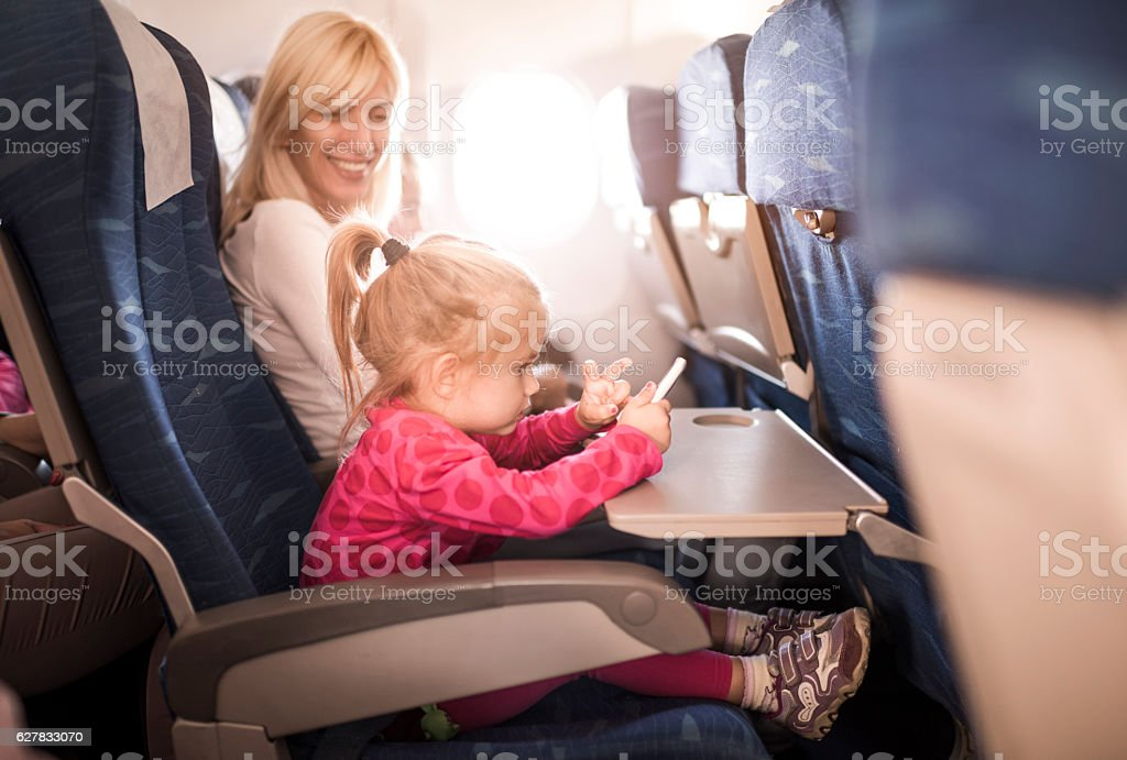 Small girl using smart phone while traveling with her mother. stock photo