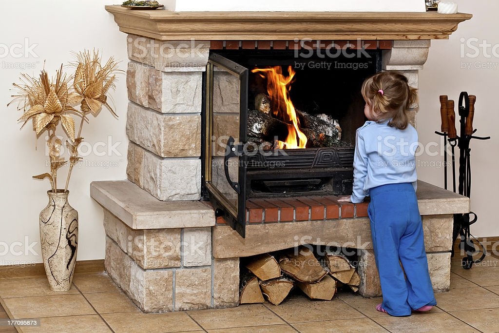 Small girl warms by the fireplace stock photo
