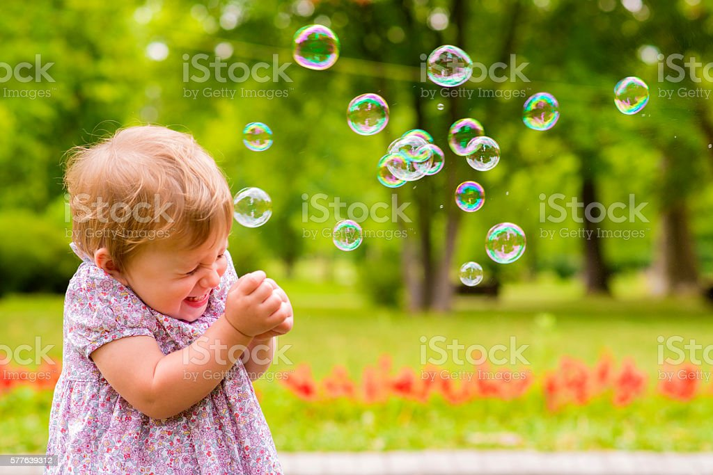 Small Girl with soap bubbles outside smiling stock photo