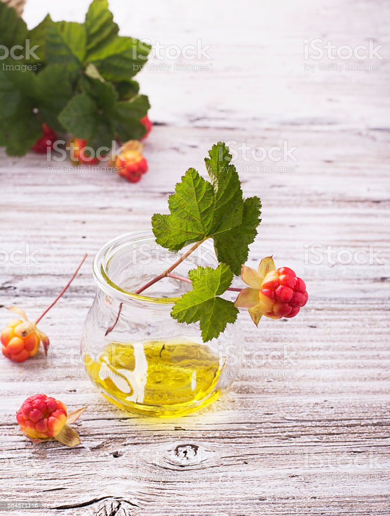 small glass jar with  rare northern cloudberry oil  berries and stock photo