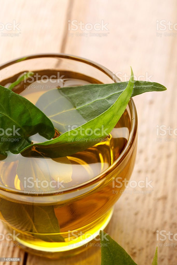 Small glass of tea with herbal leaves royalty-free stock photo