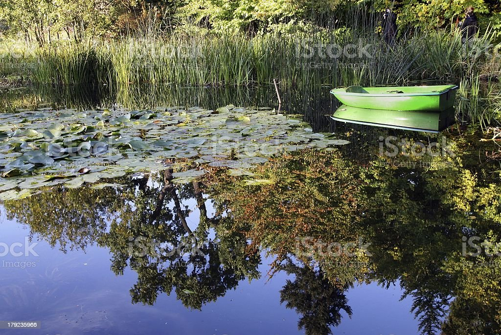 small green boat on pond and flora royalty-free stock photo