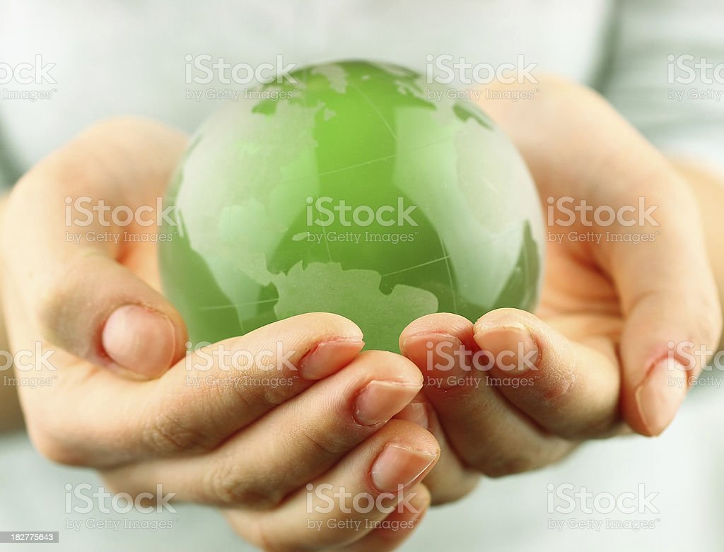 Small green globe in two cupped hands stock photo