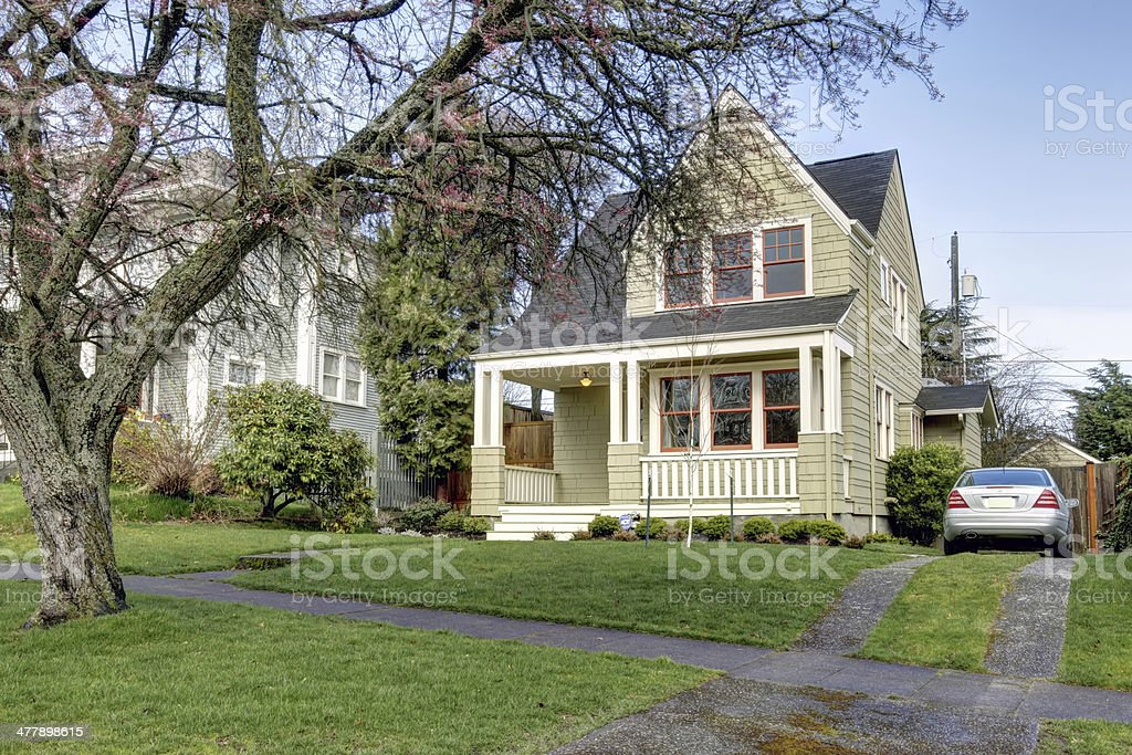 Small green house front exterior with car. stock photo