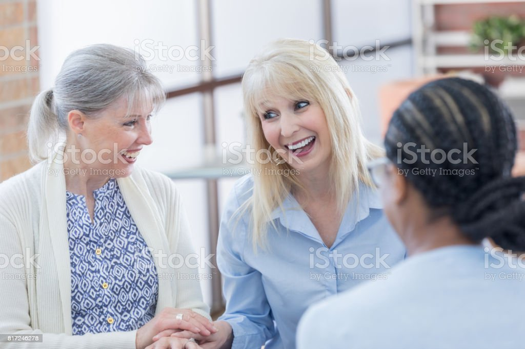 A mid adult woman and senior adult woman greet each other on the day...