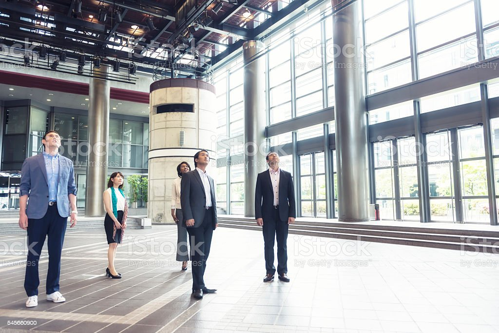 Small group of business people in bright business loby stock photo