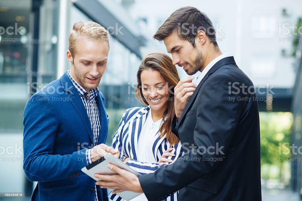 Small group of business people looking at digital tablet stock photo