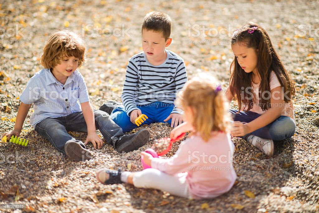 Small group of children playing at the playground. stock photo