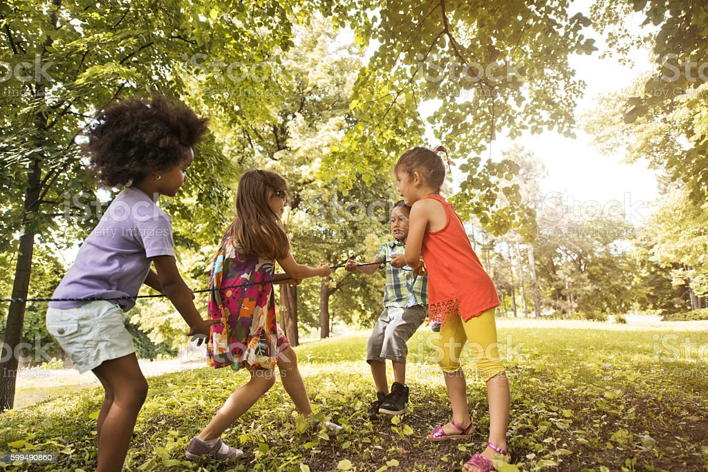 Small group of children pulling a rope in nature. stock photo
