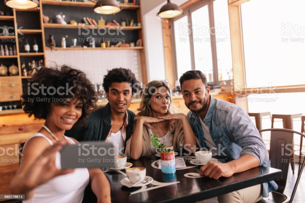 Small group of friends taking selfie at cafe stock photo