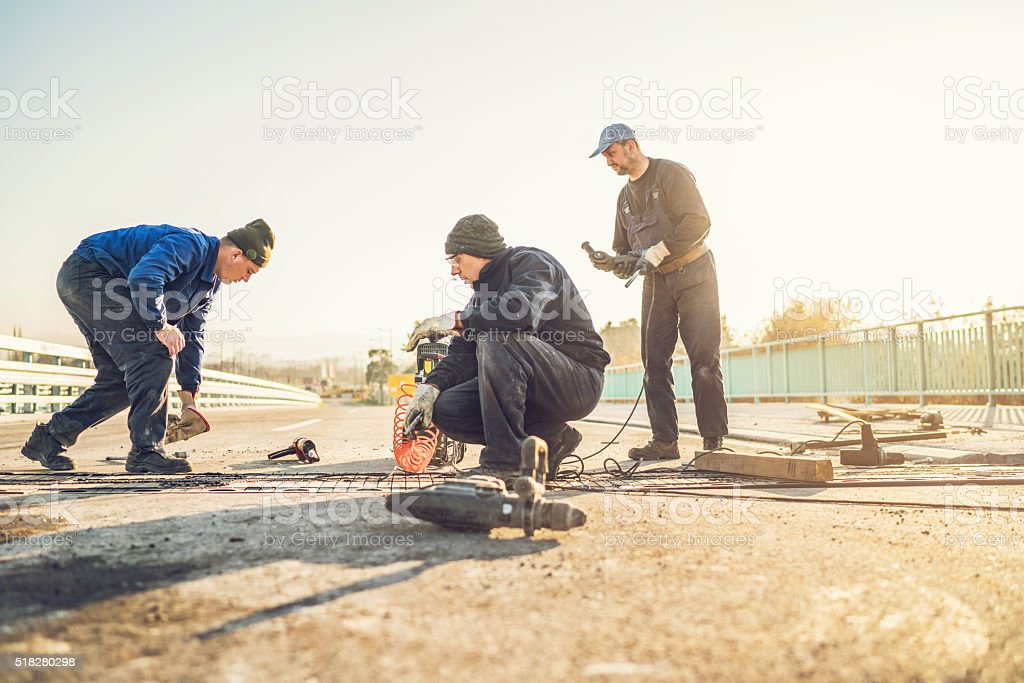 Small group of road construction workers working together. stock photo