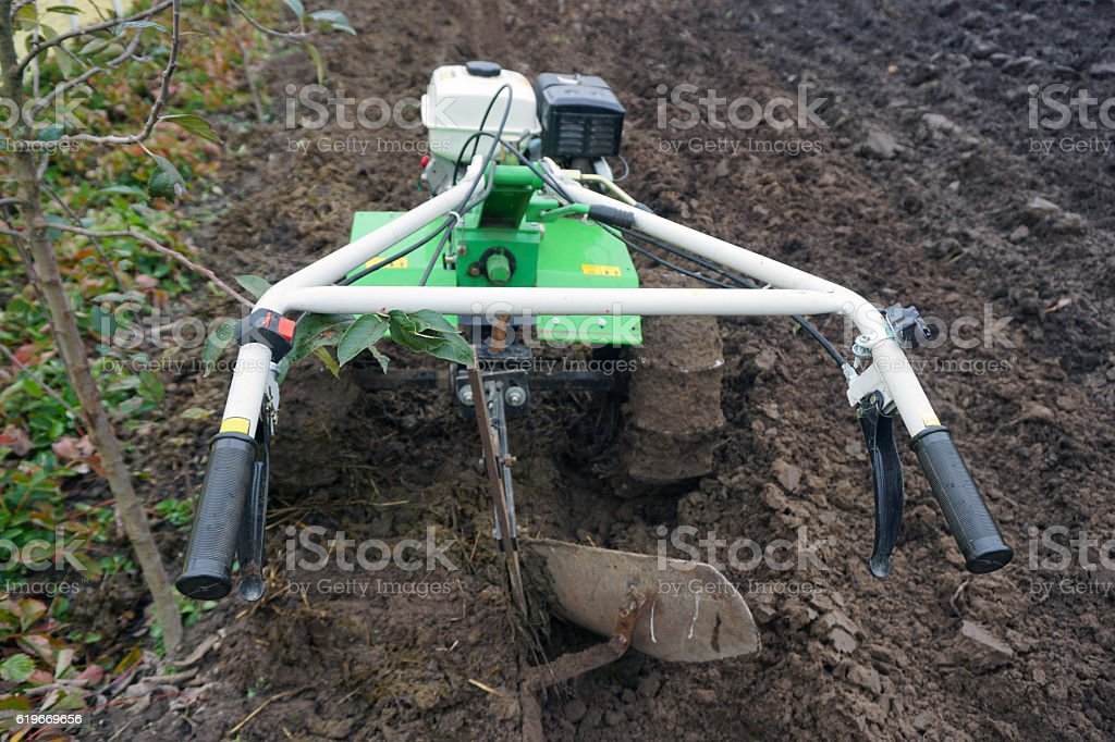 Small hand cultivator tractor in the garden stock photo