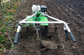 Small hand cultivator tractor in the garden