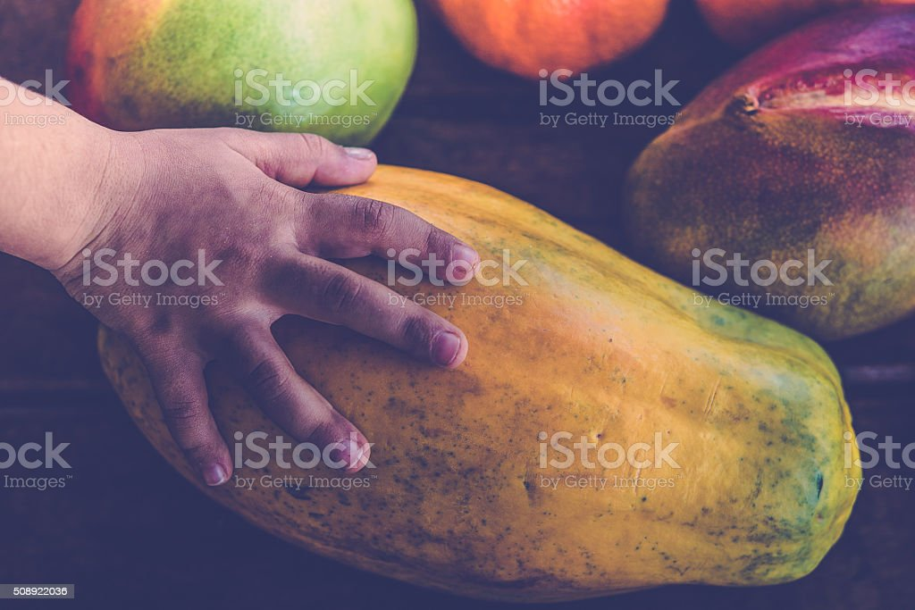 small hand touching  tropic fruits on rustic wooden background stock photo
