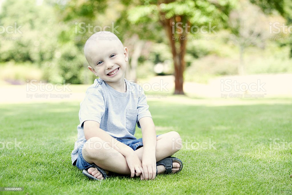 A small happy child sitting on the grass stock photo