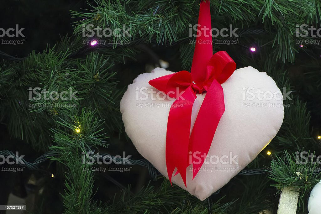 Small heart shape pillow decorated on a christmas tree stock photo