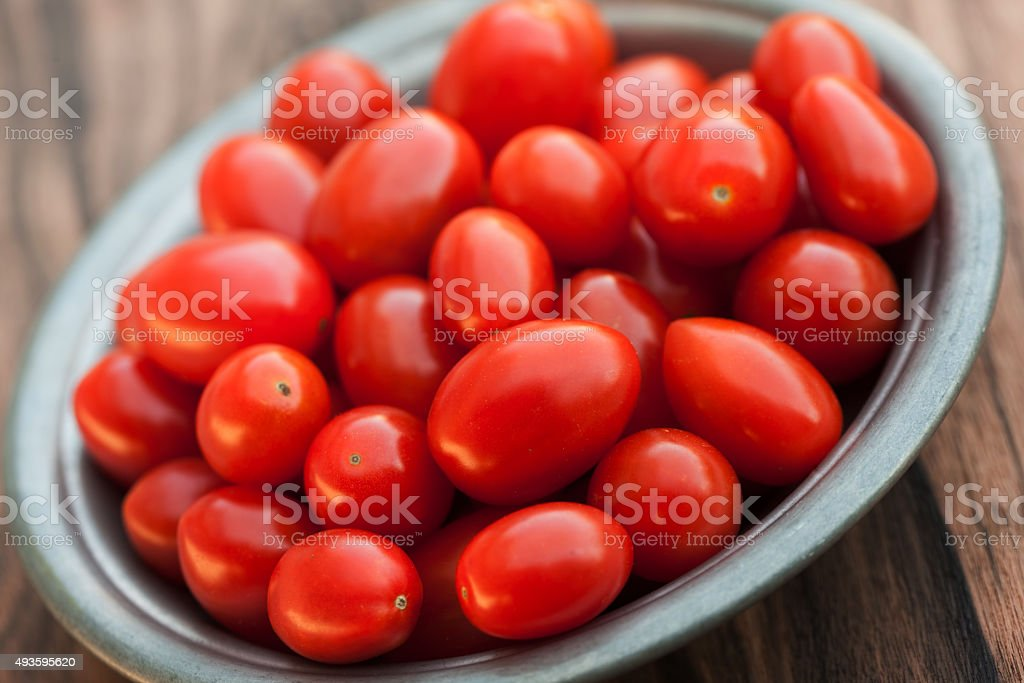 Small heirloom tomatoes in ceramic bowl stock photo