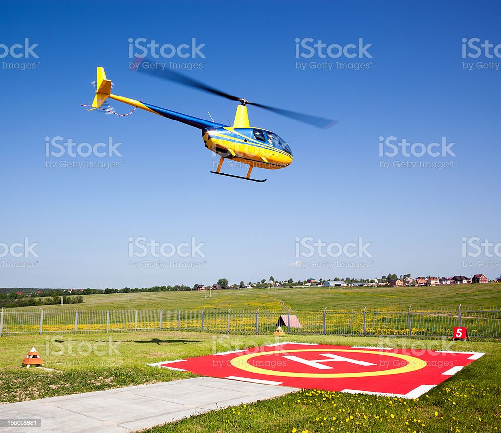 Small helicopter taking off from heliport royalty-free stock photo
