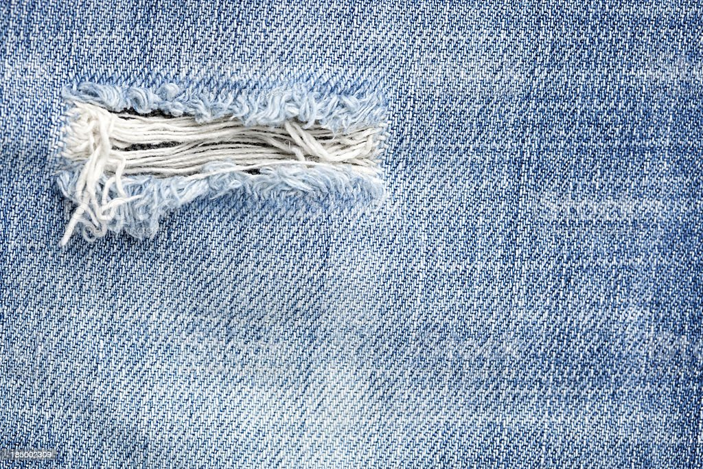 Small hole in denim jeans. royalty-free stock photo
