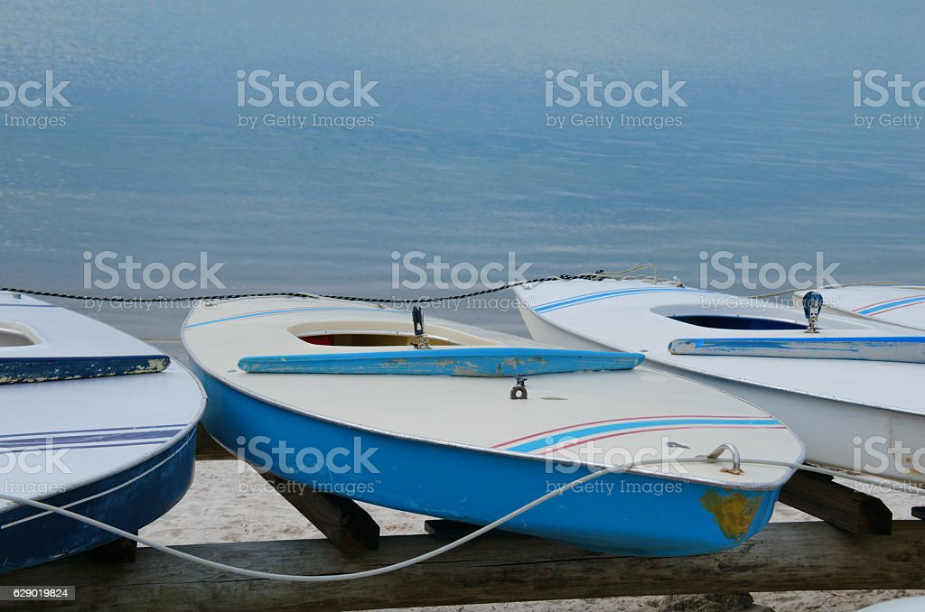 Small hollow body board style sailing dinghy sailboats on racks stock photo