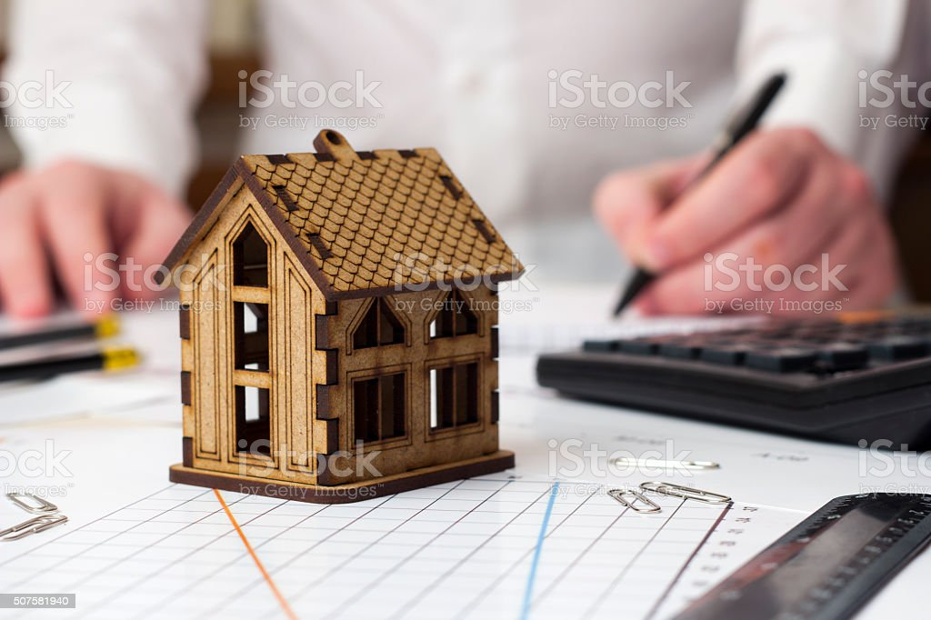 small house and a man in the background taking notes stock photo