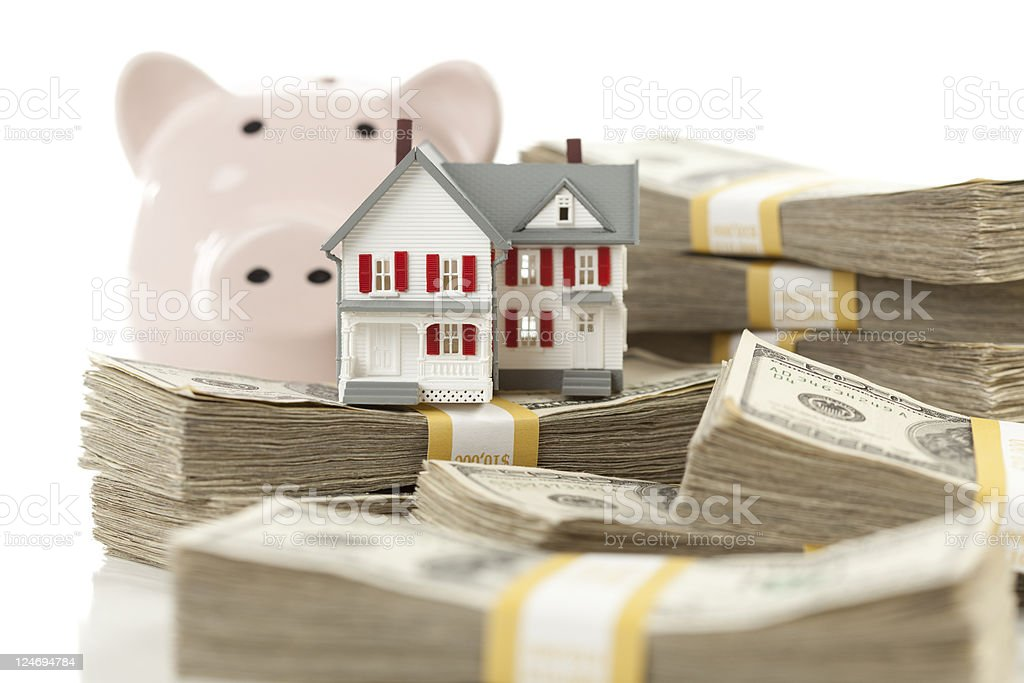 Small House and Piggy Bank with Stacks Money royalty-free stock photo