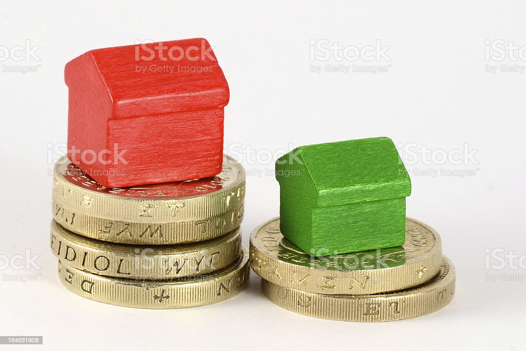 Small house in red and green on top of a gold coins royalty-free stock photo