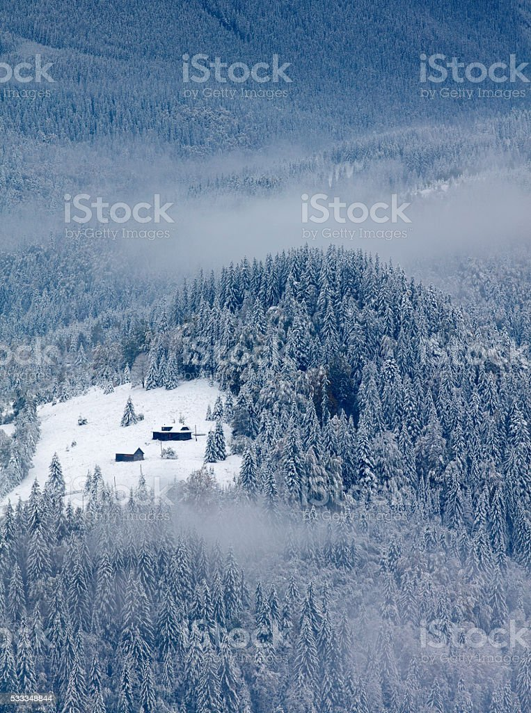 Small house in winter mountains stock photo