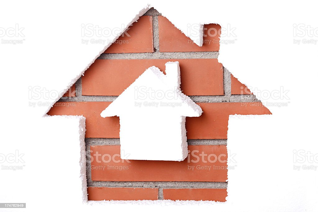 Small house inside a larger house shape on brick background stock photo