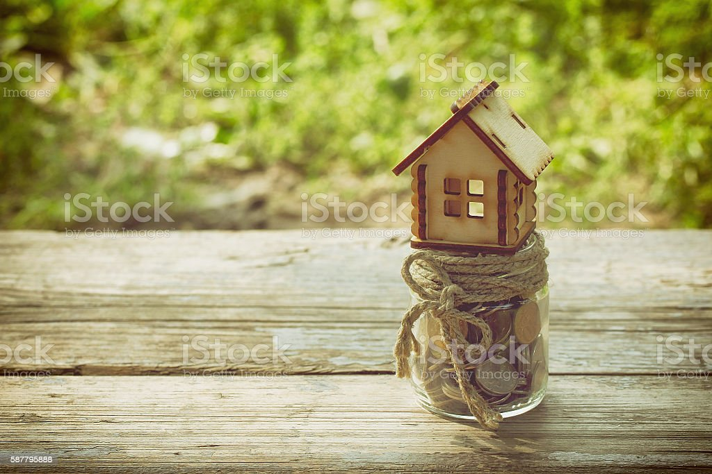 small house, jar with coins on wooden table stock photo