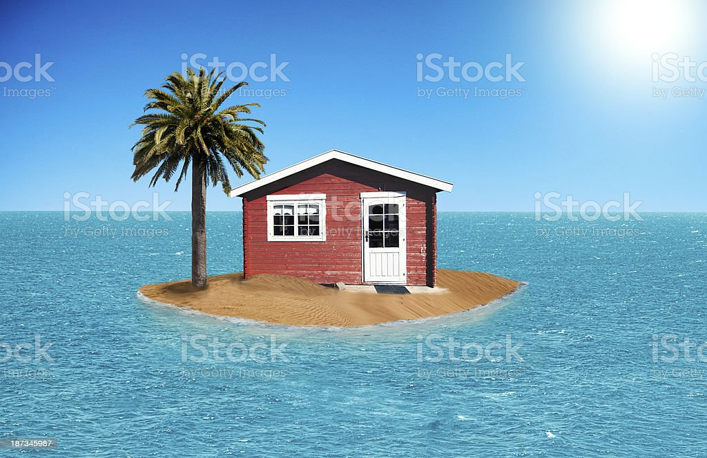 Small house on a tiny island with palm tree stock photo