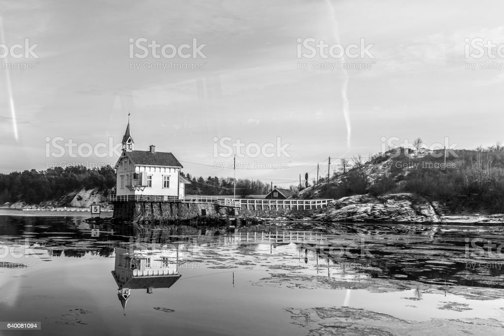 Small house on water in black and white stock photo