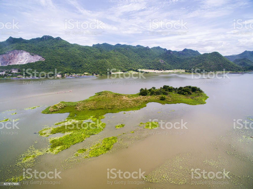 Small island and duckweed in river with mountains background stock photo