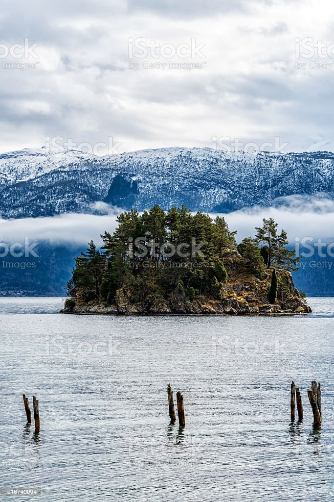 Small island by mountain range stock photo