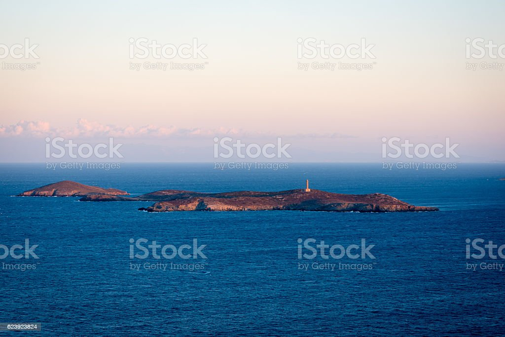 Small island with an isolated lighthouse in the sunset stock photo